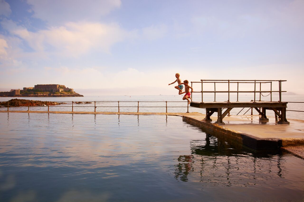 Children jump into Guernsey bathing pools